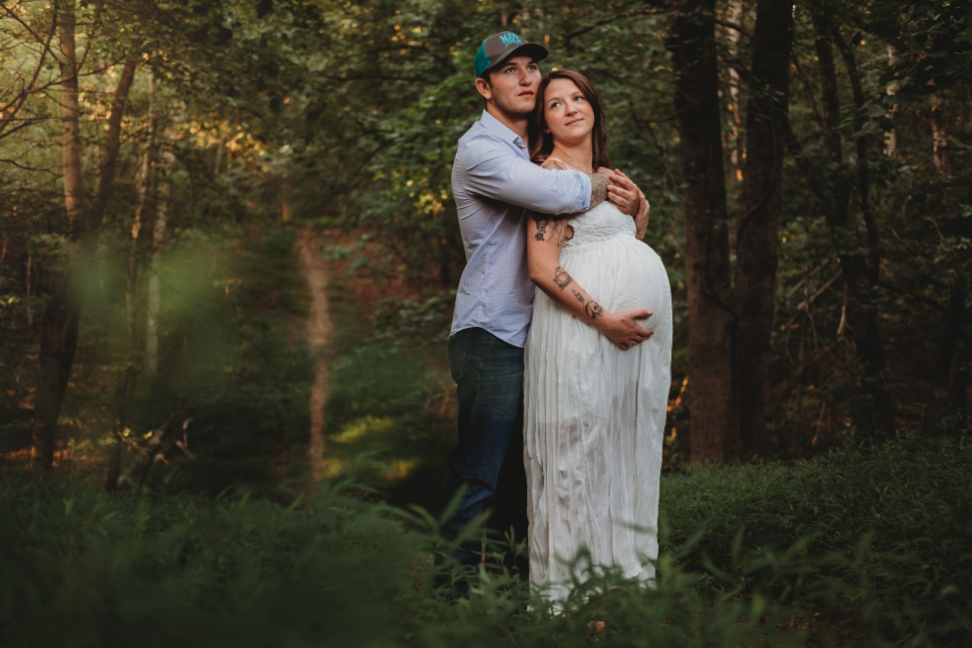 Best Maternity and Newborn Photographer Washington DC Maryland Virginia pregnant couple walking in green forest with white dress