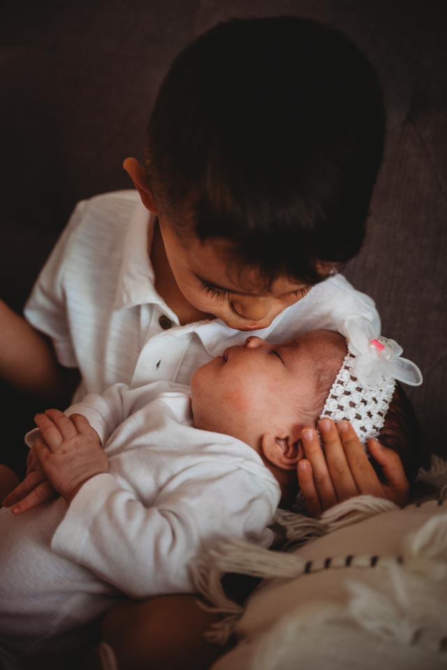 Best Maternity and Newborn Photographer Washington DC Maryland Northern Virginia - toddler boy kissing his newborn sister on the nose while cradling her head