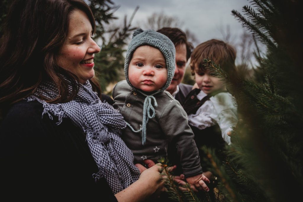 Best Maternity and Newborn Photographer Washington DC Maryland Northern Virginia family looking at christmas trees on tree farm with baby, toddler, and parents dressed for winter